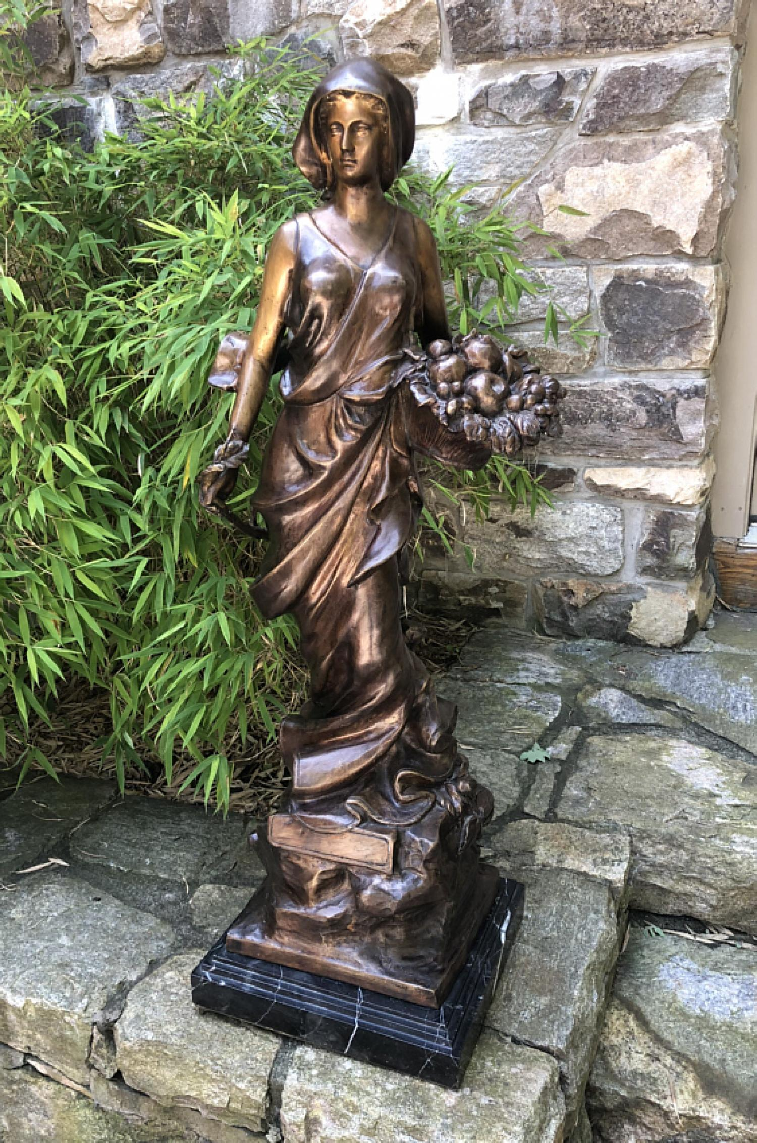 Tall bronze sculpture of a young woman