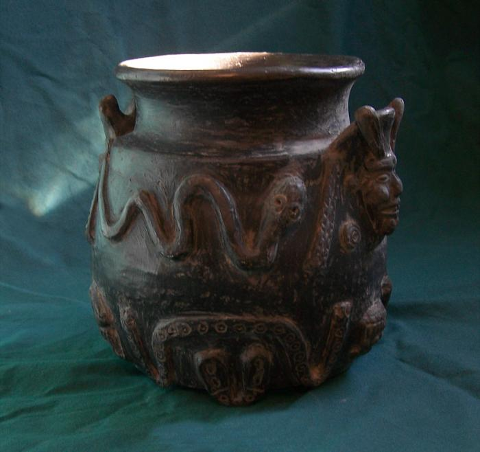 Mexican black ware pottery jar with heads and serpents